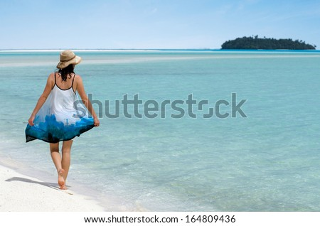 Young woman walks on Aitutaki Lagoon Cook Islands. women freedom, travel, vacation ,happy, happiness, solo, alone, single, fun.