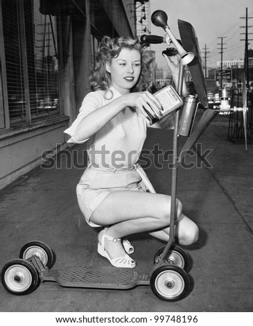 Young woman wants her scooter to fly - stock photo