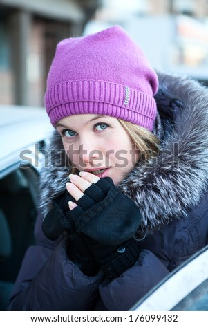 Young woman warming fingers on the hands with gloves, getting into car - stock photo