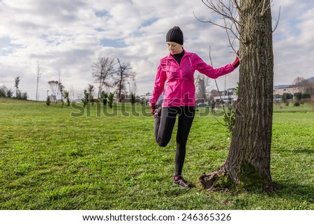 Young woman warming up and stretching the legs before running on a cold winter day in an urban park. - stock photo