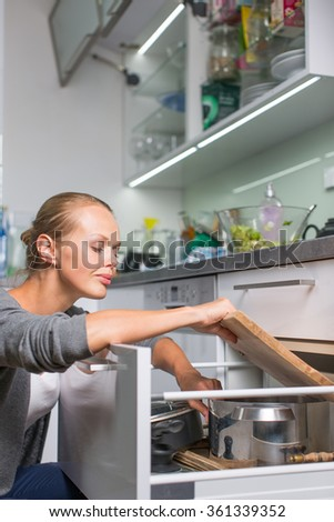 Young woman washing dishes in her modern kitchen, using a dishwasher, putting the dishes in their place - stock photo