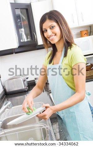 young woman washing dishes in kitchen - stock photo
