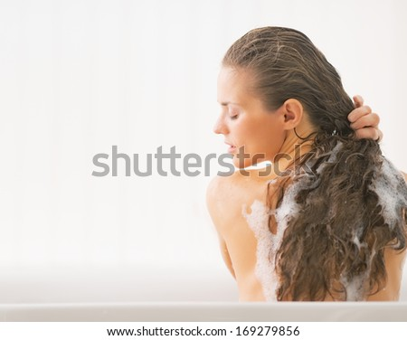 Young woman washing hair in bathtub - stock photo