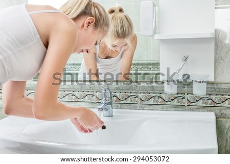 Young woman washing her face and hands with clean water in bathroom - stock photo