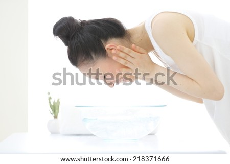 young woman washing her face in bathroom - stock photo