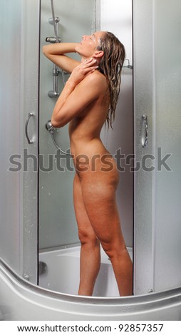 Young woman washing her perfect body in a shower.