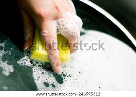 Young woman washing the pan with the yellow sponge - stock photo