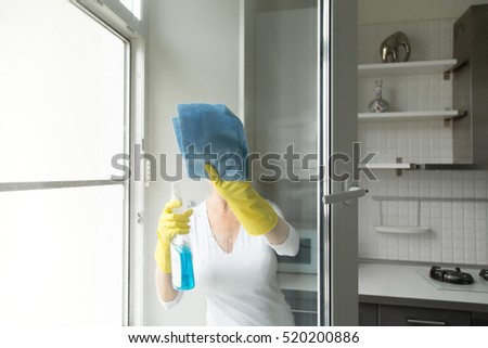 Young woman washing the windows, wearing rubber protective yellow gloves, with rag and spray bottle detergent. Focus on the rag, face unseen. Home, housekeeping concept