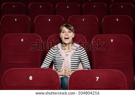 Young woman watching a fun scene of the comedy - stock photo