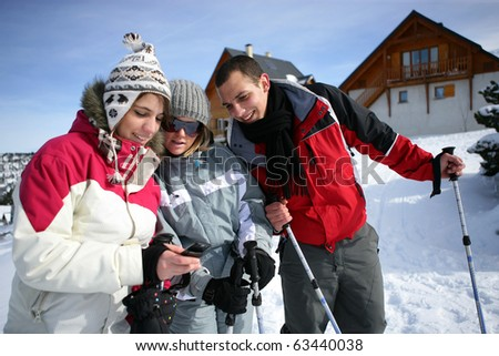 Young woman watching her mobile phone near friends in snow - stock photo