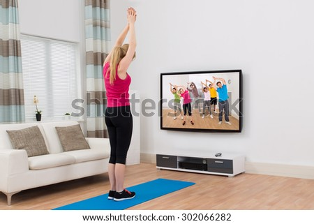 Young Woman Watching Television And Exercising In Living Room At Home - stock photo