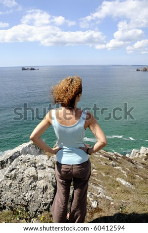 Young woman watching the coastline of the atlantic ocean in Brittany, France - stock photo