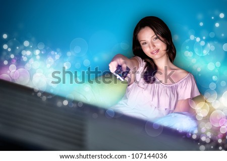 Young woman watching TV sitting on the beanbag at home - stock photo