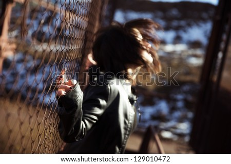 Young woman waving her hair on urban blurry environment - stock photo