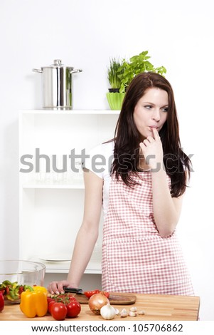 young woman wearing a apron in her kitchen sucking her finger - stock photo
