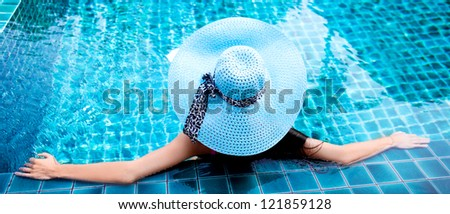 young woman wearing a blue hat sitting in the swimming pool