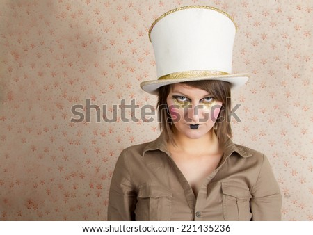 young woman wearing a creative visage and a white top hat    - stock photo