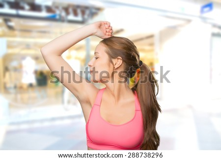 Young woman wearing a gym clothes. She is kissing her biceps. Over shopping center background - stock photo