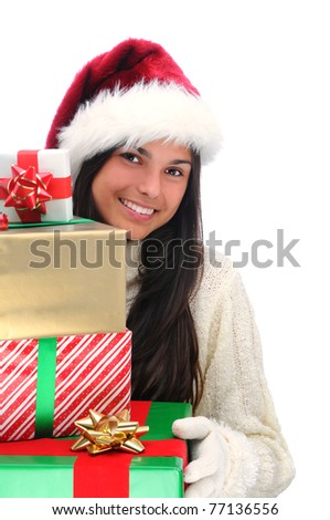 Young woman wearing a Santa Claus hat holding a large stack of assorted Christmas presents. Vertical format isolated on white.