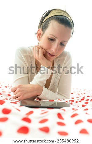 Young woman wearing an alice band in her hair lying browsing on digital tablet or  e-book on her bed on a red and white polka dot bedspread. - stock photo