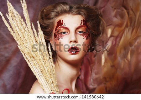 young woman wearing ball dress with bright make up holding  dry branches - stock photo