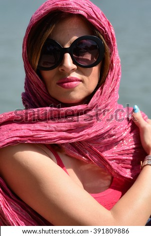 young woman wearing big sun glasses and pink scarf around her head relaxing outside crossed arms - stock photo