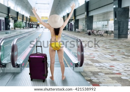 Young woman wearing bikini with a suitcase walking to escalator at airport - stock photo