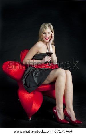 young woman wearing black dress with a glass of red wine - stock photo