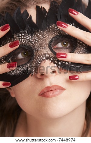 Young woman wearing black feathered carnival mask - stock photo