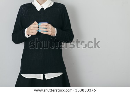 young woman wearing black sweater and skirt holding a cup of coffee - stock photo
