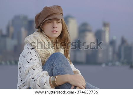 Young woman wearing brown kepi and knitting sweater sitting on the beach/ cityscape in the background