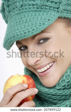 Young woman wearing cap and scarf, holding apple, portrait