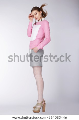 Young woman wearing casual clothes posing at studio. Full length. - stock photo