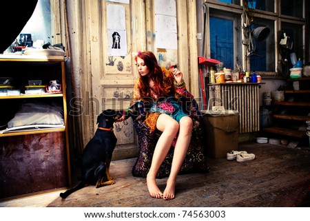 young woman wearing colorful clothes in art studio sit by the door with  her dog - stock photo
