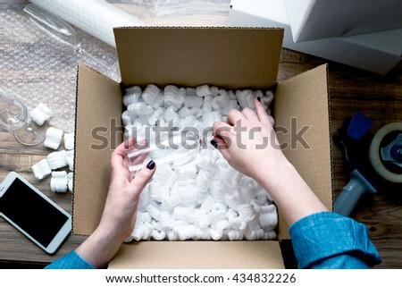 Young woman wearing denim shirt preparing for moving. Packing, selling online, shipping, moving and lifestyle concept - stock photo