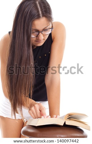 young woman wearing glasses and reading a book - stock photo