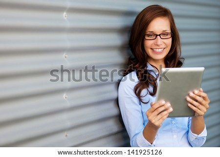 Young woman wearing glasses leaning against a corrugated metal wall or door reading her tablet computer, angled with copyspace - stock photo