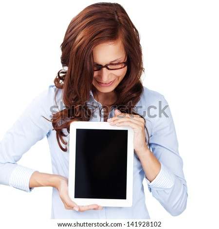 Young woman wearing glasses looking down at a blank tablet computer screen with copyspace that she is holding on front of her chest - stock photo