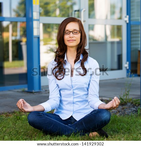 Young woman wearing glasses with a serene expression sitting meditating on green grass in front of a commercial building or college - stock photo