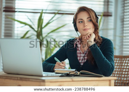 Young woman wearing headphones and studying  - stock photo