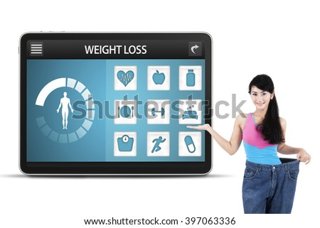 Young woman wearing her old jeans and showing weight loss applications on the screen, isolated on white background - stock photo