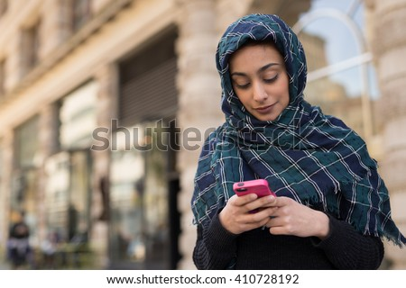 Young woman wearing hijab head scarf in city texting cell phone