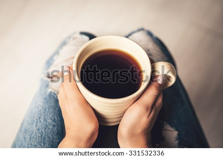 Young woman, wearing in blue jeans, cup of coffee. manicure - stock photo