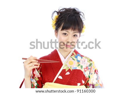 Young woman wearing Japanese kimono with chopsticks, isolated on white background.