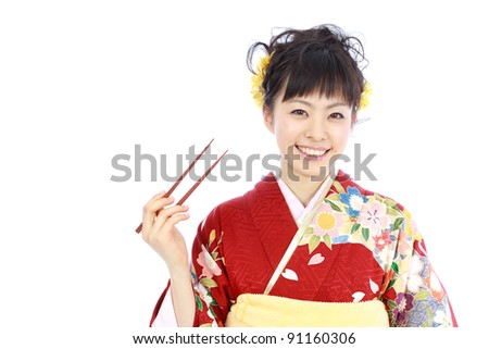 Young woman wearing Japanese kimono with chopsticks, isolated on white background. - stock photo