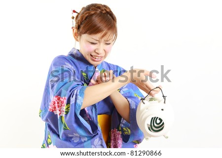 Young woman wearing Japanese kimono with mosquito coil ,bitten by mosquito - stock photo