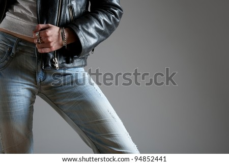 Young woman wearing jeans and black leather jacket. - stock photo