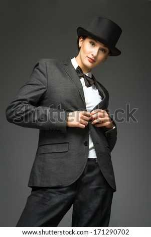 Young woman wearing man's suit posing over grey background. Woman feels like a man - concept. Retro style young woman against grey background.