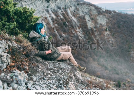 Young woman wearing parka jacket and cargo pants resting in the mountains and looking into the distance