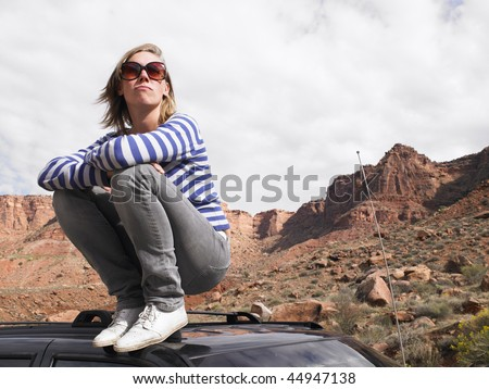 Young woman wearing stripped shirt on roof of car desert landscape in background. Horizontal shot. - stock photo